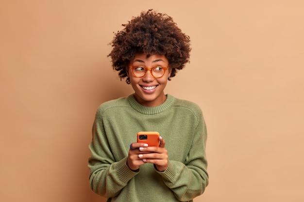 Portret van knappe vrouw gebruikt mobiele telefoon ontvangt aangenaam bericht breed glimlacht en kijkt bedachtzaam opzij leest feedback onder haar bericht in sociale netwerken geïsoleerd op beige muur