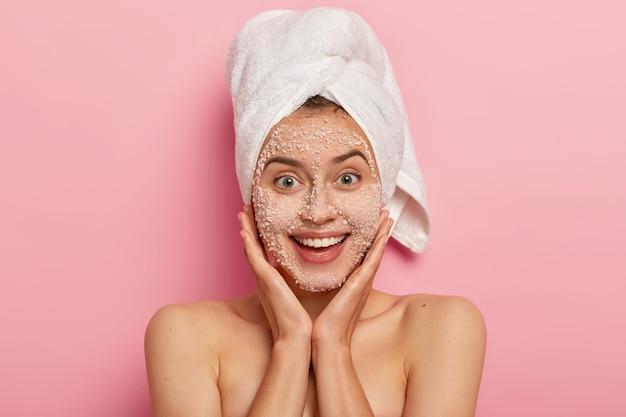 Portret van knappe vrouw raakt zachtjes wangen, heeft blote schouders, gladde gezonde huid, lacht aangenaam, past peelig scrub op gezicht toe, geïsoleerd op roze achtergrond, draagt badhanddoek