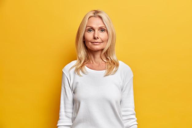 Portret van knappe vrouw van middelbare leeftijd met gerimpeld gezicht natuurlijke schoonheid blond haar kijkt direct camera heeft rustige uitdrukking gekleed in witte casual trui
