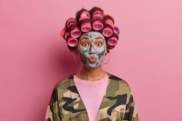 Portret van knappe vrouw zorgt voor haar huid, kleimasker toepast op gezicht, kapsel maakt met haarrollers, terloops gekleed poseert tegen roze houdt lippen afgerond wil iemand kussen