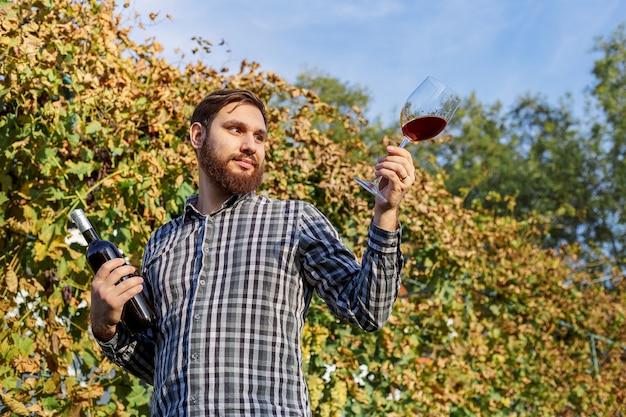 Portret van knappe wijnmaker die de wijnkwaliteit controleert