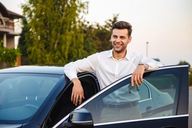 Portret van knappe zakelijke man met pak, staande in de buurt van zijn luxe zwarte auto met open bestuurdersdeur