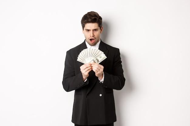 Portret van knappe zakenman in trendy pak, geschrokken kijken naar geld, prijs gewonnen, staande op een witte achtergrond.