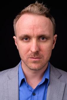 Portret van knappe zakenman met blond haar tegen zwarte muur