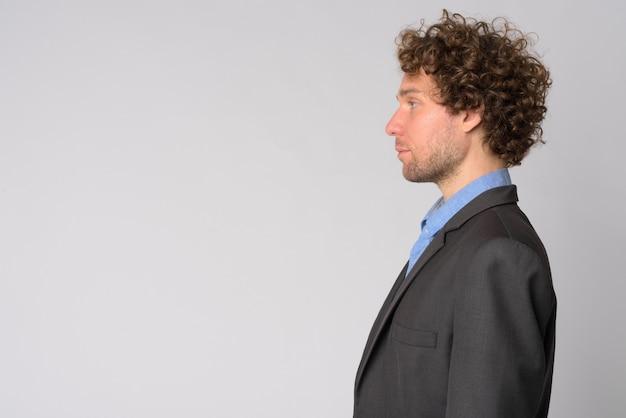 Portret van knappe zakenman met krullend haar op wit