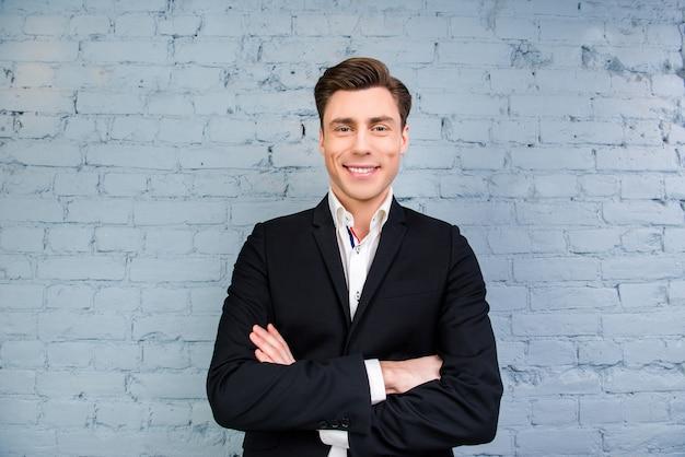 Portret van knappe zakenman met stralende glimlach en gekruiste handen