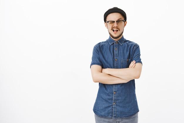 Portret van knappe zelfverzekerde en stijlvolle zelfverzekerde man in zwarte muts en bril met baard knipogen hand in hand gekruist op borst klaar en volbracht