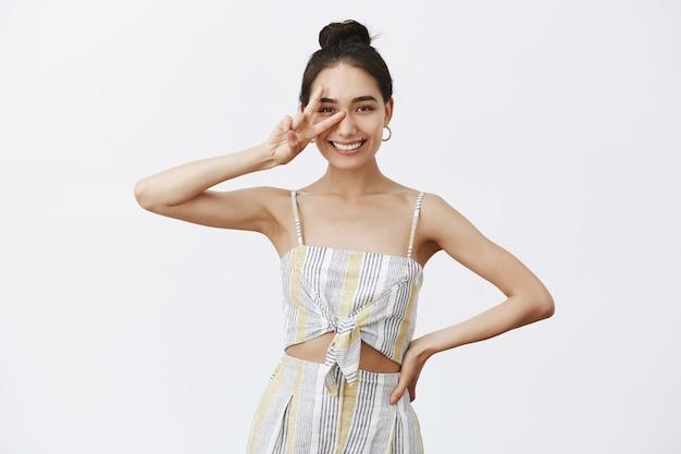 Portret van knappe zelfverzekerde gebruinde vrouw met knot kapsel, vrede of overwinningsteken boven oog tonen en breed glimlachend, hand op taille vasthouden