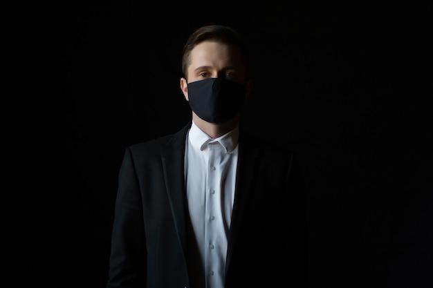 Portret van knappe zelfverzekerde jonge zakenman met medisch masker