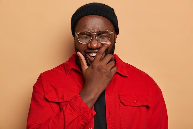 Portret van knappe zwarte man bedekt de helft van het gezicht, lacht positief, grappen met vrienden en heeft goede tijd, draagt zwarte hoed en rood shirt