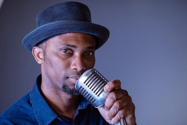 Portret van knappe zwarte man bezig met het zingen van een vintage lied. geïsoleerde man zingen etnische culturele liedjes. jonge afro-amerikaanse zanger die trendy microfoon