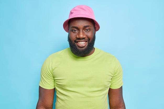 Portret van knappe zwarte man glimlacht gelukkig heeft dikke baard grote vrolijke glimlach op facewears panama en groen t-shirt glimlacht tandelijk geniet van goede dag geïsoleerd over blauwe muur