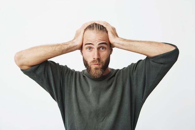 Portret van knappe zweedse man met trendy haar en baard wordt geschokt