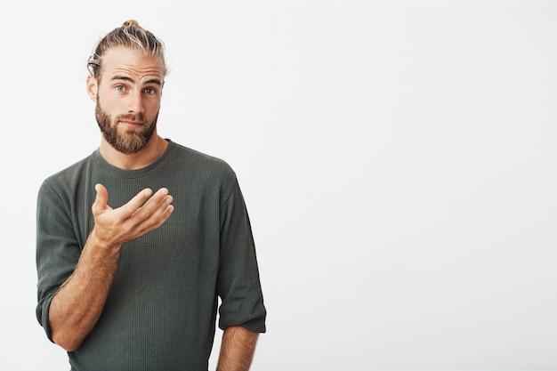 Portret van knappe zweedse man met trendy kapsel en baard in casual grijze kleding op zoek