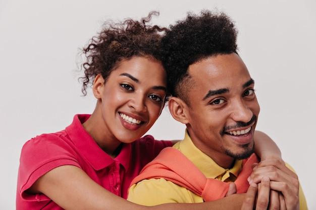 Portret van knuffelende man en vrouw in geïsoleerde muur
