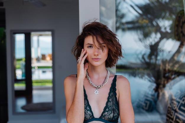 Portret van kort haar brunette vrouw met ketting op nek accessoires in groene kanten lingerie buiten villa