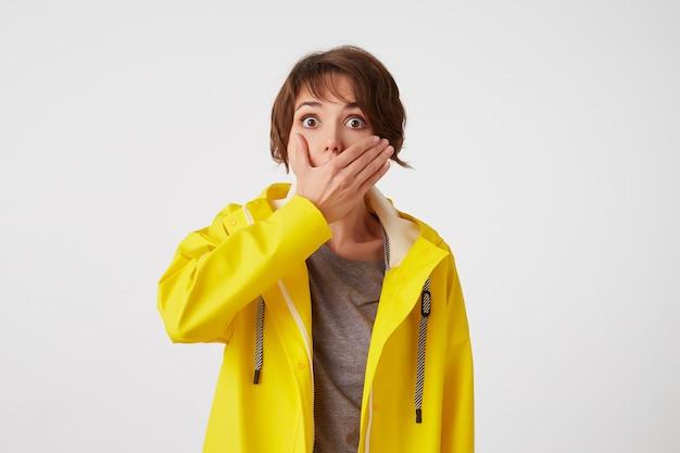 Portret van kortharige krullende vrouw in gele regenjas, hoort ongelooflijk nieuws, bedekte mond met hand, staat over witte muur met wijd open ogen met verbaasde uitdrukking.