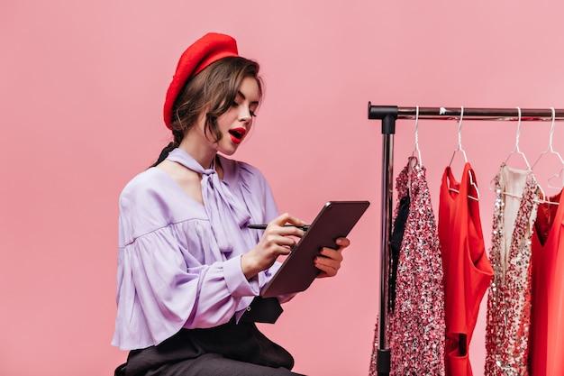 Portret van krullend meisje met rode lippenstift notities maken in tablet op roze achtergrond met dressees.