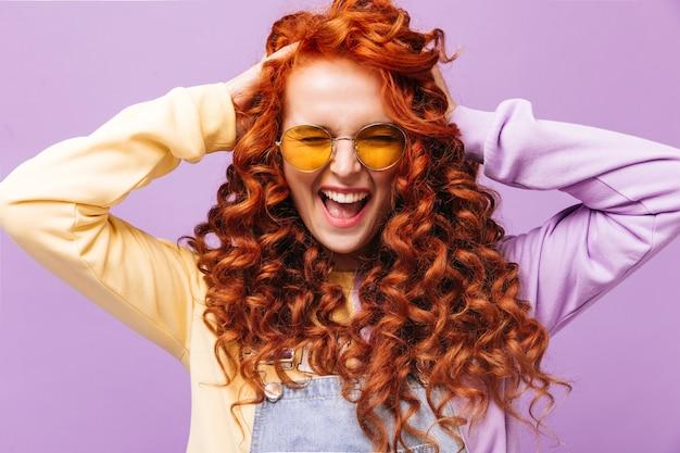 Portret van krullend ondeugend roodharig meisje in gele zonnebril poseren op geïsoleerde muur