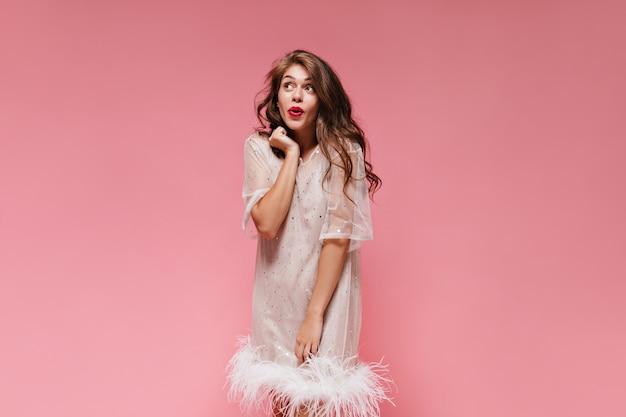 Portret van krullende brunette vrouw in witte jurk poseren in een goed humeur op roze muur