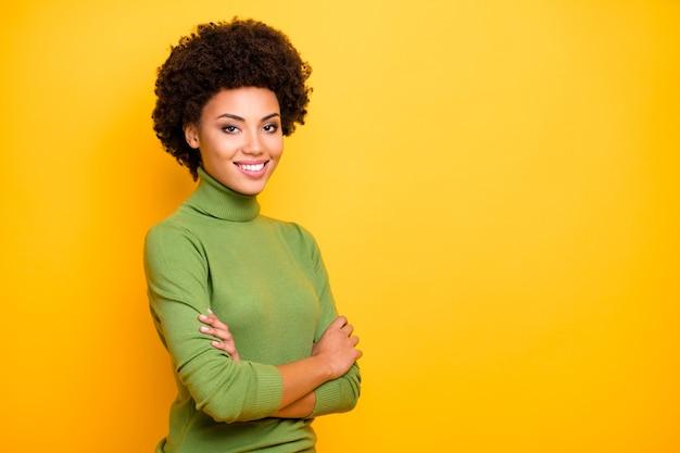 Portret van krullende golvende trendy vrolijke positieve gedraaide vrouw met gekruiste armen op zoek naar jou met brede glimlach.