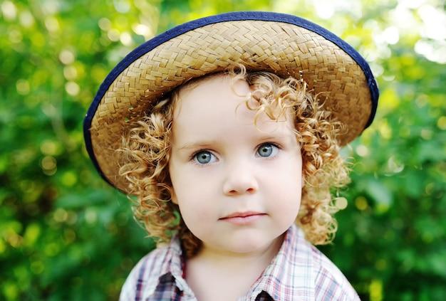 Portret van krullende roodharige baby in een hoed.