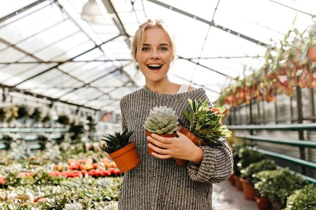 Portret van krullende vrouw in grijze trui met veel potplanten. groenogige blonde met glimlach stelt bij plantenwinkel.