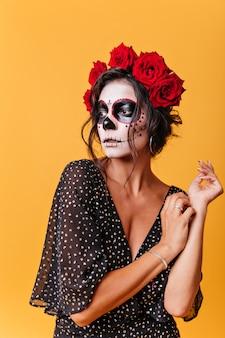 Portret van krullende vrouw met rode grote rozen in haar haar die op mysterieuze wijze afstand tegen muur van oranje muur onderzoeken. meisjesmodel uit mexico met make-up voor poseren voor halloween