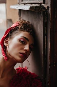 Portret van krullende vrouw op houten deur