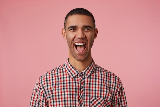 Portret van lachen aantrekkelijke donkere man in geruit overhemd, kijkt naar de camera met gelukkige uitdrukking en wijd open mond, hoort grappige grap, staat op roze achtergrond.