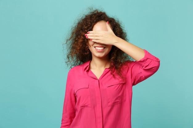 Portret van lachend afrikaans meisje in roze casual kleding die ogen bedekt met hand geïsoleerd op blauwe turquoise muur achtergrond in studio. mensen oprechte emoties, lifestyle concept. bespotten kopie ruimte.