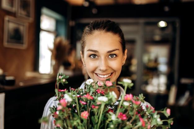 Portret van lachend brunette meisje met boeket van roze en witte chrysanten.