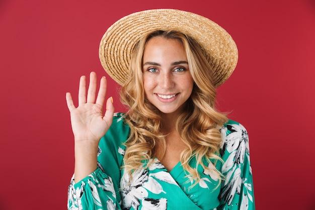 Portret van lachend gelukkig jong blond meisje in felblauwe jurk poseren geïsoleerd over rode muur zwaaiend naar jou