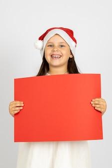 Portret van lachend grappig meisje in witte jurk en kerstman hoed met rode lege banner met kopie...