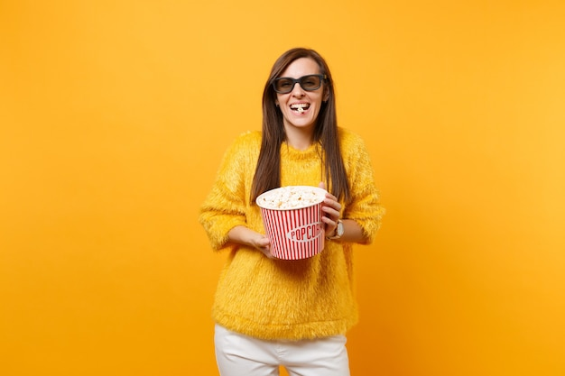 Portret van lachend jong meisje in 3d imax-bril die filmfilm kijkt, eet popcorn uit emmer geïsoleerd op felgele achtergrond. mensen oprechte emoties in de bioscoop, lifestyle concept. ruimte kopiëren.