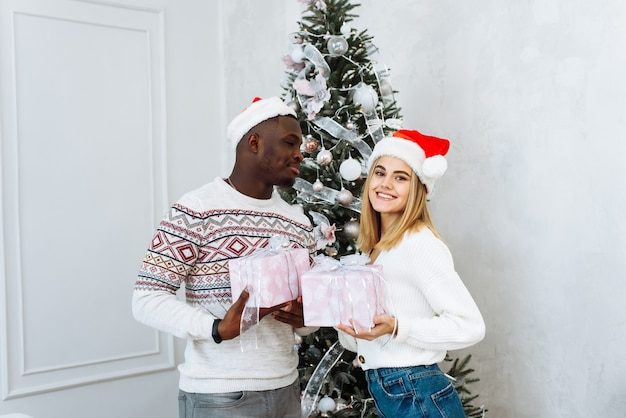 Portret van lachend jong stel in de buurt van kerstboom vieren samen nieuwjaar. gelukkige man en vrouw genieten van wintervakantie in de buurt van versierde dennenboom