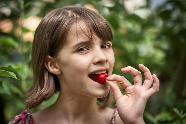 Portret van lachend meisje dat kersen eet in de tuin