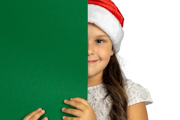 Portret van lachend meisje in kerst gnome hoed verbergen half gezicht achter zwarte groene banner geïsoleerd...