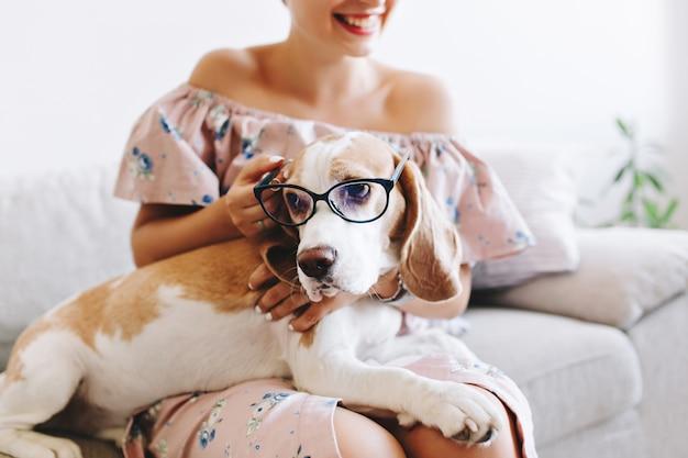 Portret van lachend meisje in roze jurk met droevige beagle hond in glazen op voorgrond
