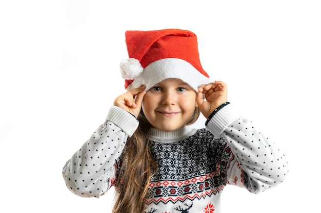 Portret van lachend meisje in witte gebreide kerstsweater met rendieren met kerstman hoed is...