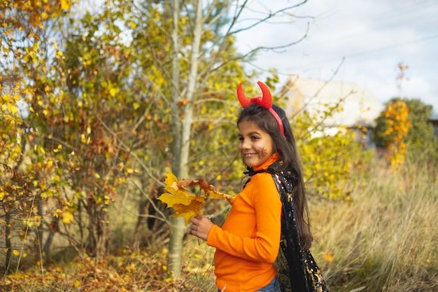 Portret van lachend meisje met bruin haar rennen en springen. grappige kinderen in carnavalskostuums buitenshuis.