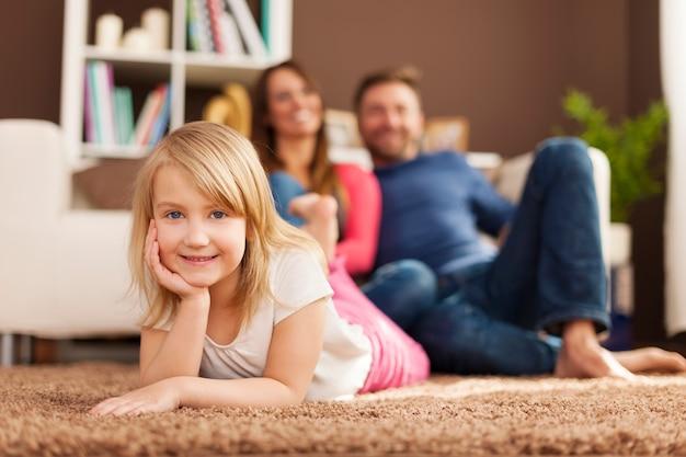 Portret van lachend meisje ontspannen met haar ouders thuis