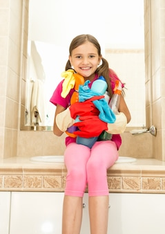 Portret van lachend meisje poseren met reinigingsmiddelen in flessen in de badkamer