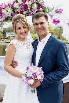Portret van lachend net getrouwd stel poseren onder florale decoratieve boog