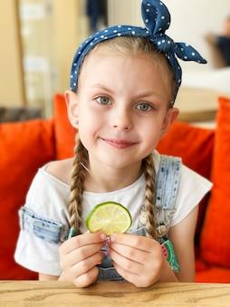 Portret van lachend schattig klein meisje met schijfjes limoen