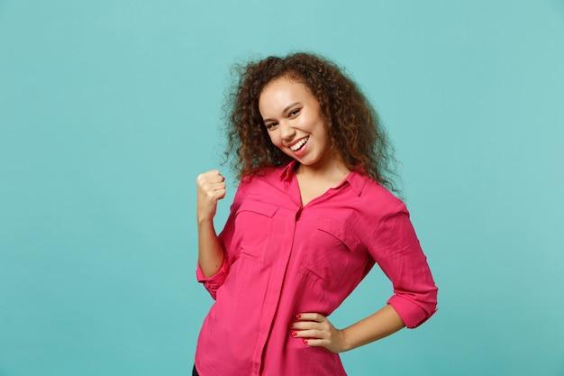Portret van lachend vrij afrikaans meisje in roze casual kleding die winnaargebaar doet geïsoleerd op blauwe turquoise muurachtergrond in studio. mensen oprechte emoties levensstijl concept. bespotten kopie ruimte. Gratis Foto