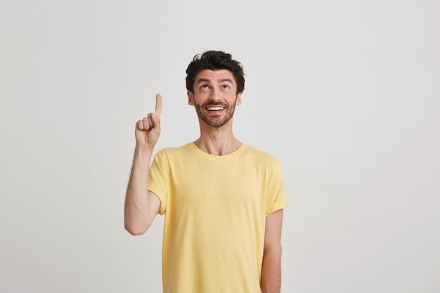 Portret van lachende aantrekkelijke bebaarde jonge man draagt gele t-shirt ziet er blij uit en wijst met de vinger op wit wordt geïsoleerd