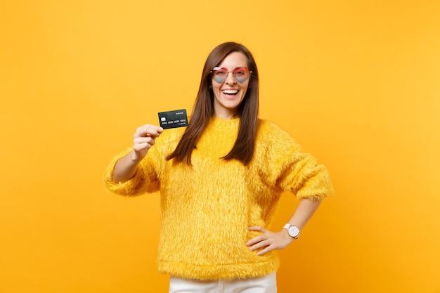 Portret van lachende aantrekkelijke jonge vrouw in bont trui, hart bril met creditcard geïsoleerd op heldere gele achtergrond. mensen oprechte emoties, lifestyle concept. reclame gebied.