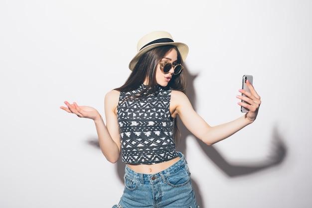 Portret van lachende aantrekkelijke vrouw in hoed staan en het nemen van een selfie geïsoleerd dan wit