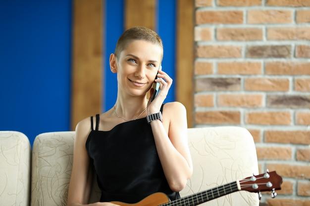 Portret van lachende aantrekkelijke vrouw praten op mobiele telefoon. kortharige dame zittend op comfortabele bank binnenshuis. de jonge ukelele van de vrouwenholding. muziek en vrije tijd thuis concept